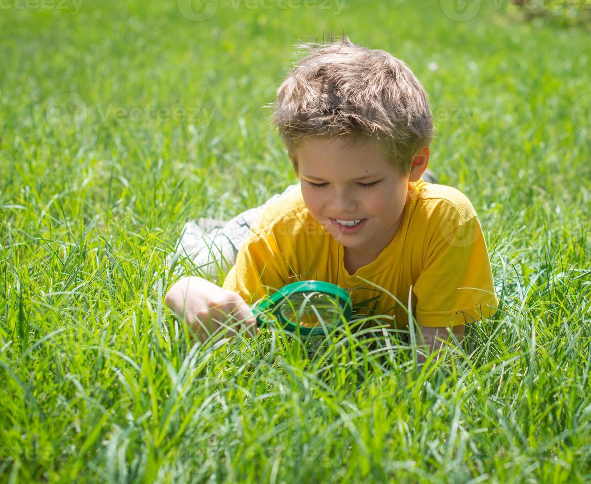 Kid with magnifying glass outdoors. Happy boy enjoying sunny summer. photo
