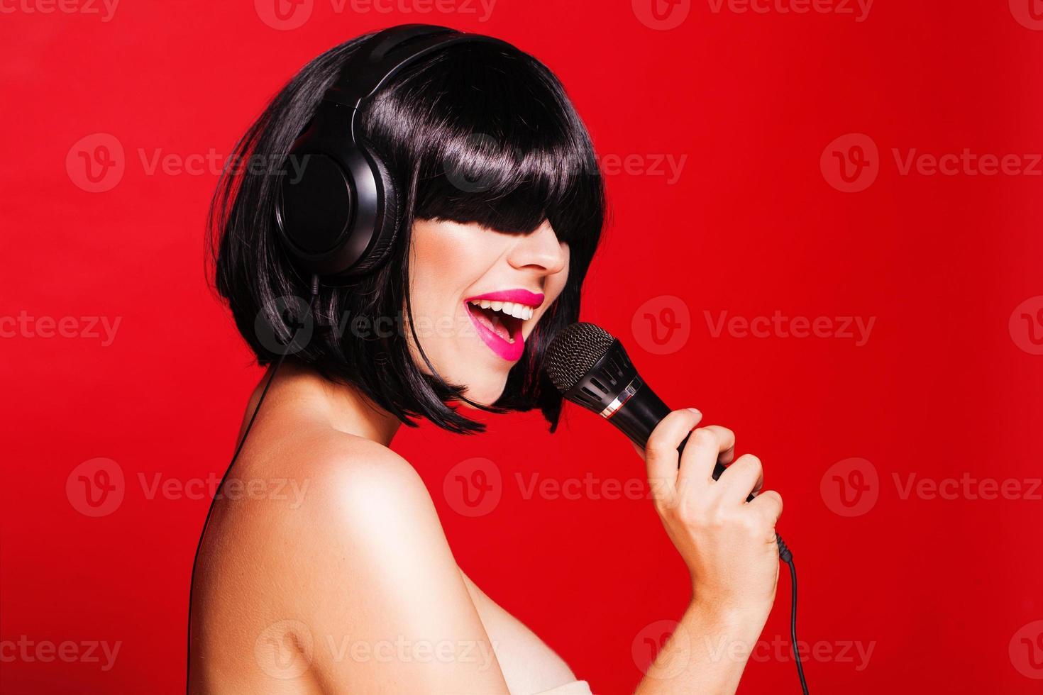 Mujer con micrófono cantando con auriculares y disfrutando de un baile foto
