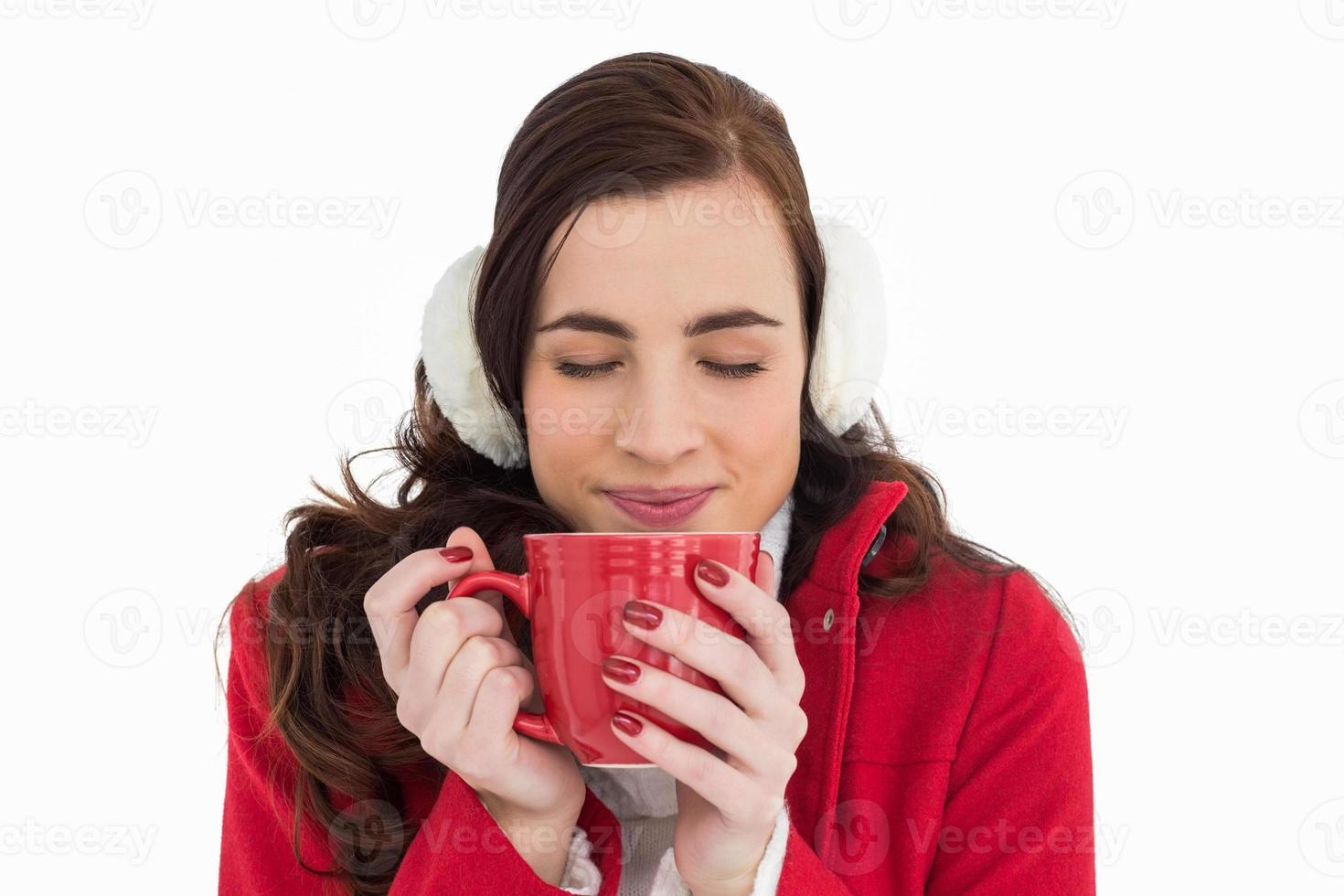 Mujer en ropa de invierno disfrutando de una bebida caliente con los ojos cerrados foto