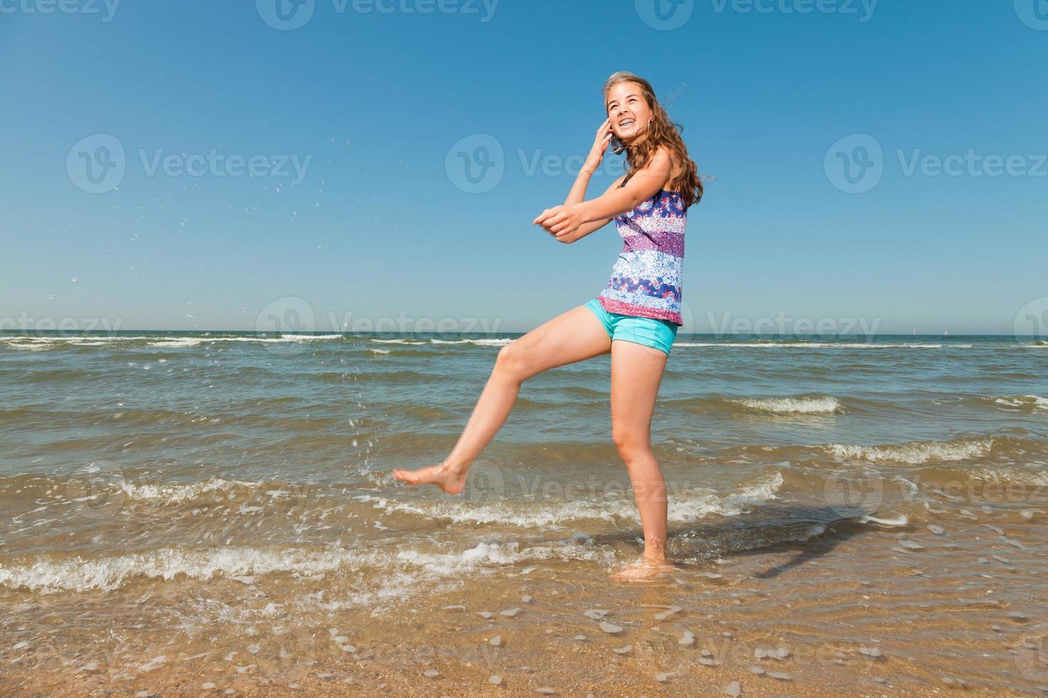 Niña feliz con el pelo largo y castaño disfrutando de la refrescante playa. foto