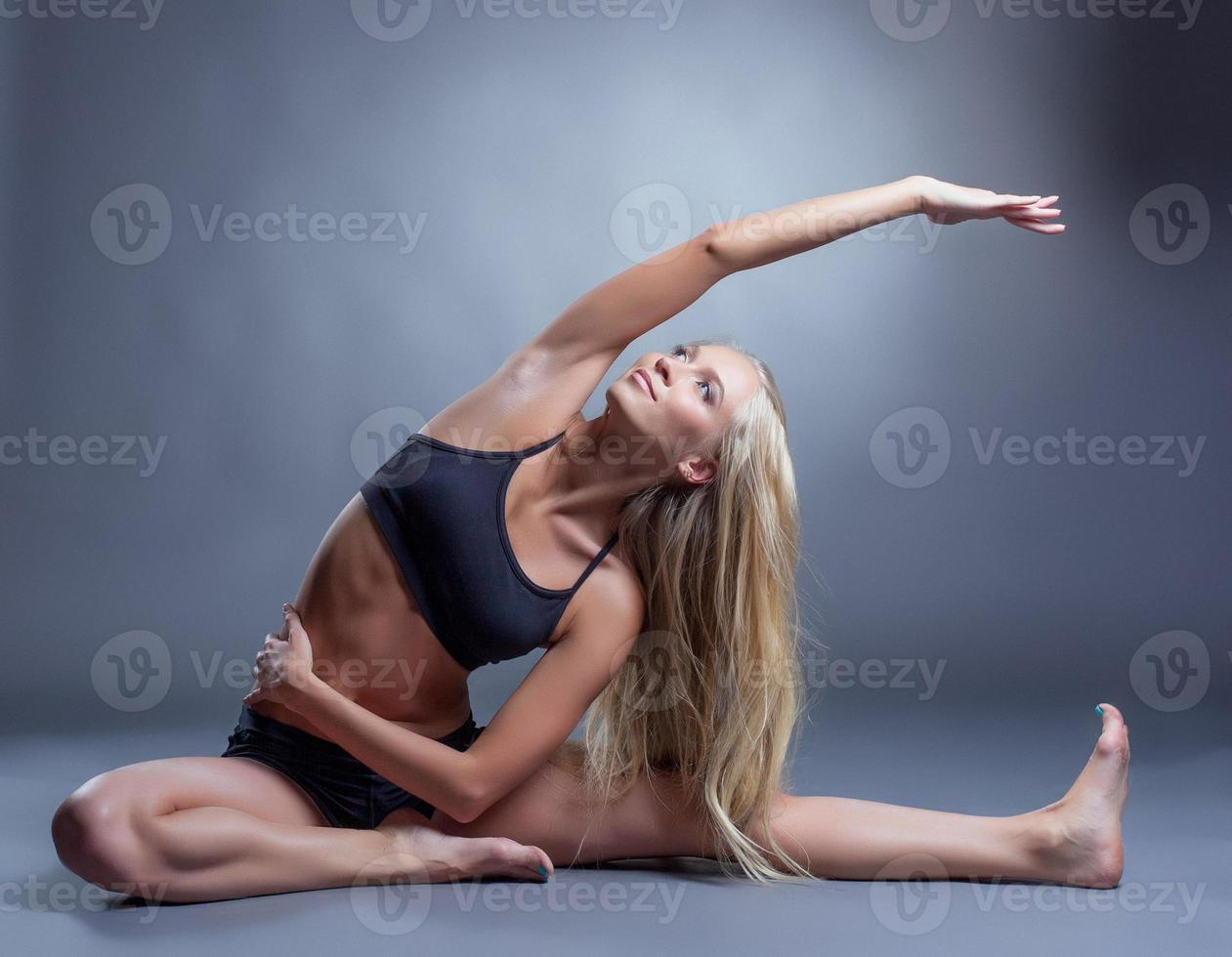 Image of smiling young woman doing stretching photo