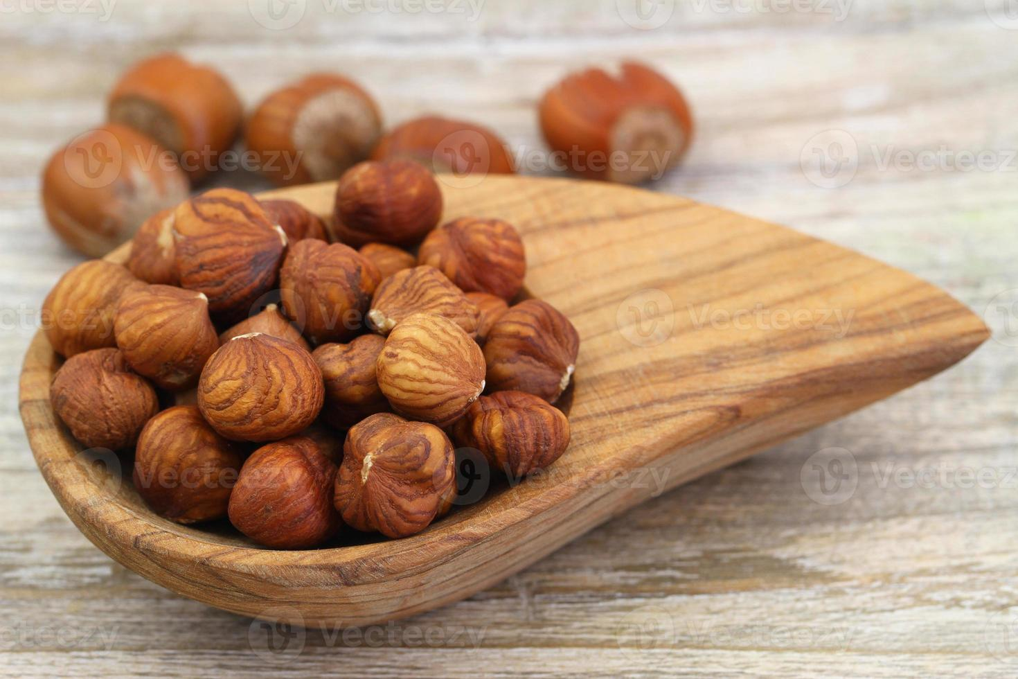 Hazelnuts in miniature wooden bowl, close up photo