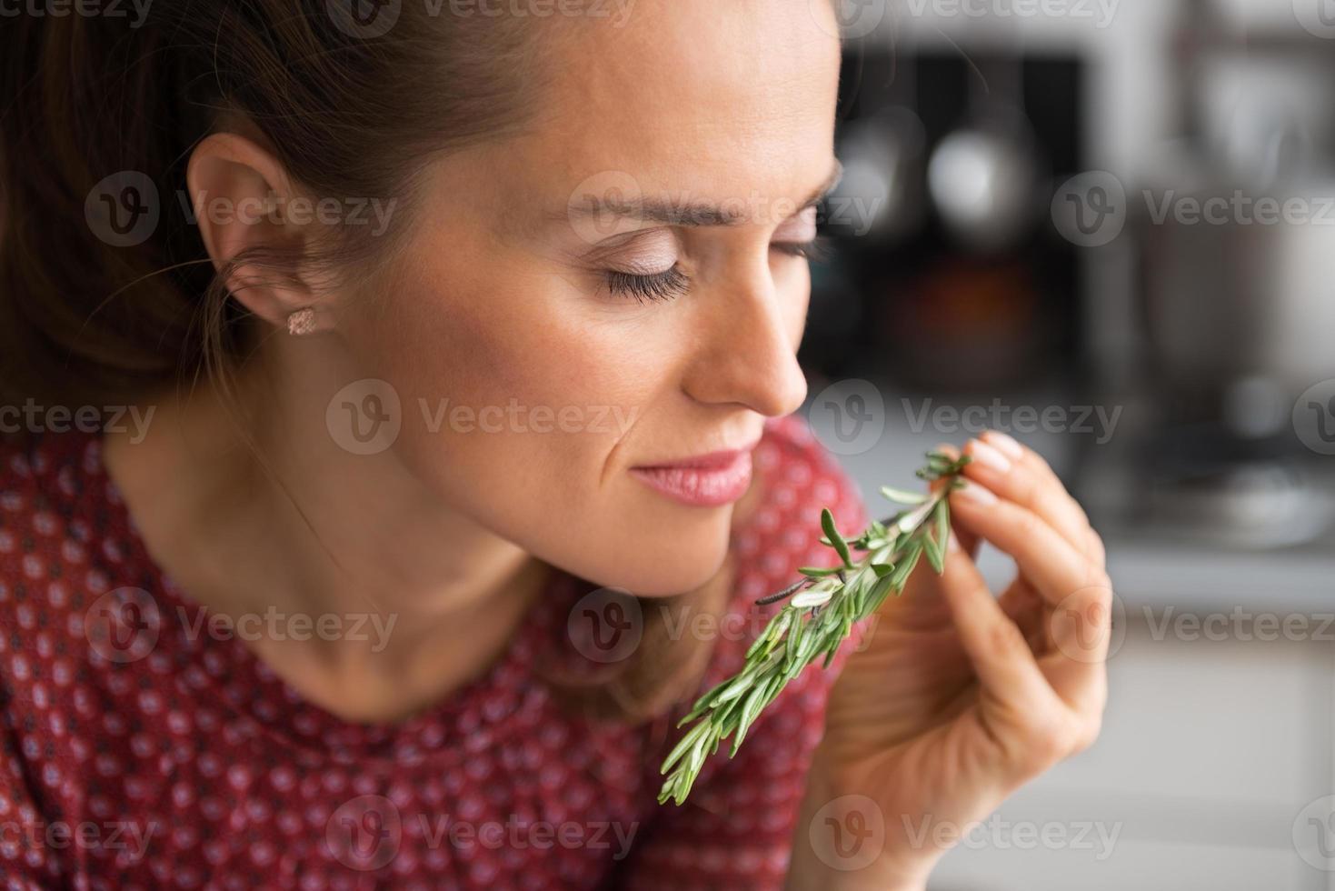 joven ama de casa disfrutando rosmarinus fresco foto