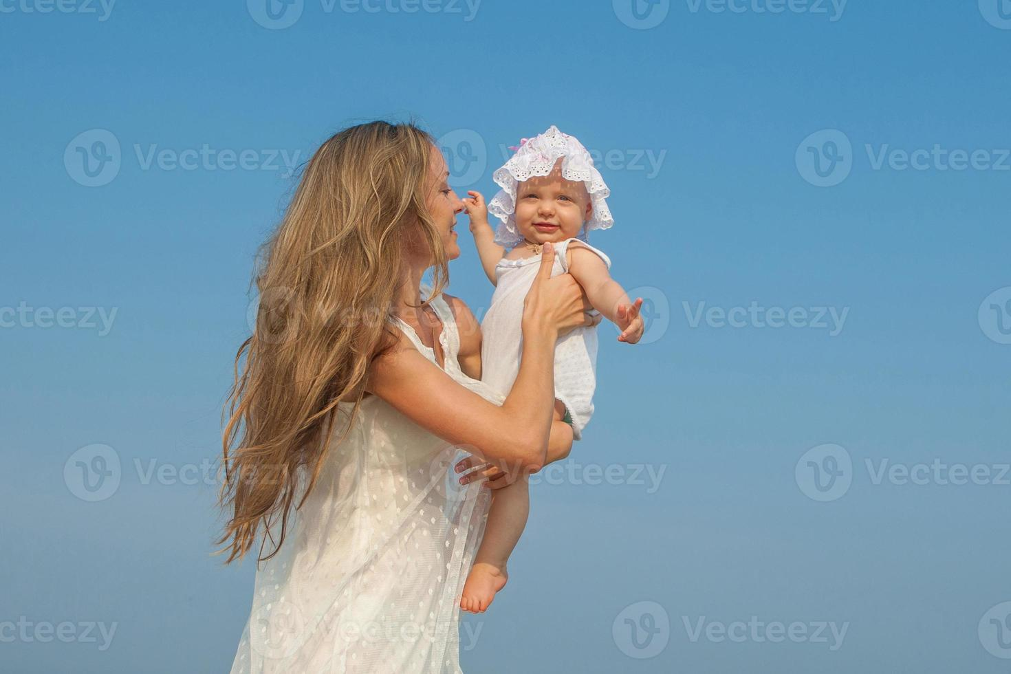 Happy beautiful mother and daughter enjoying beach time photo
