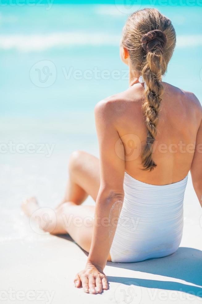 Mujer joven sentada en la playa. vista trasera foto