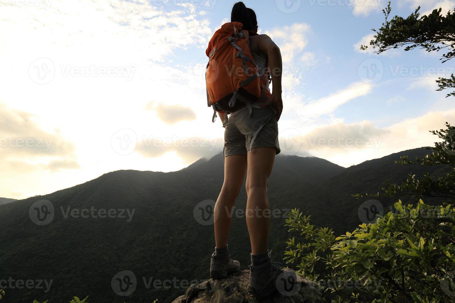 mujer mochilero en el pico de la montaña disfruta de la vista foto