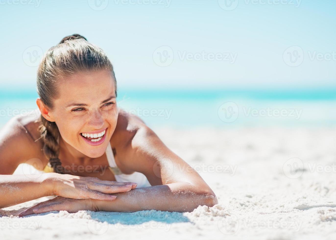 sonriente mujer joven en traje de baño disfrutando acostado en la playa foto