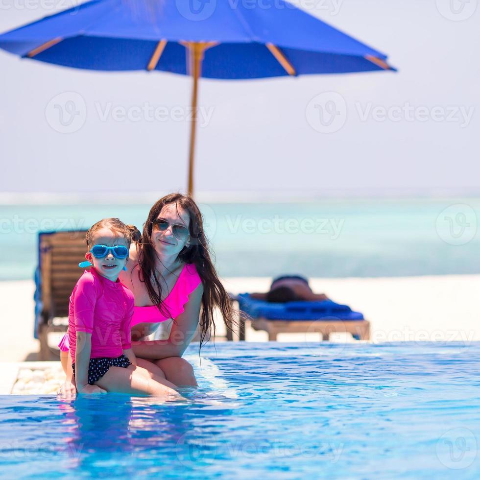 Niña linda y feliz madre disfrutando de vacaciones en la piscina foto