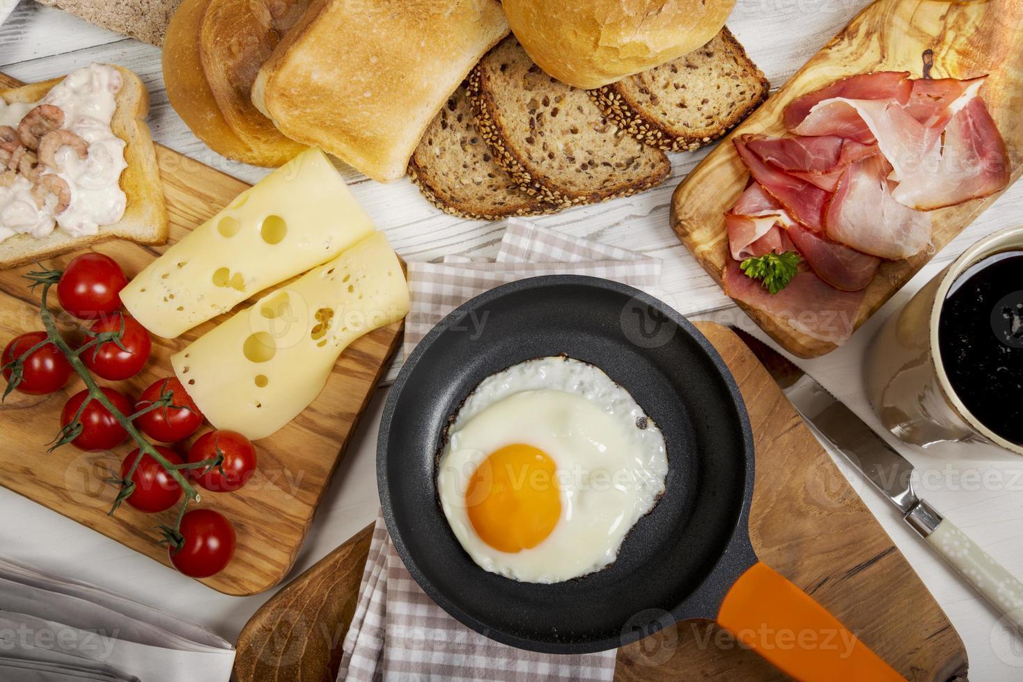 huevo frito en sartén, queso, jamón, pan y bollos foto