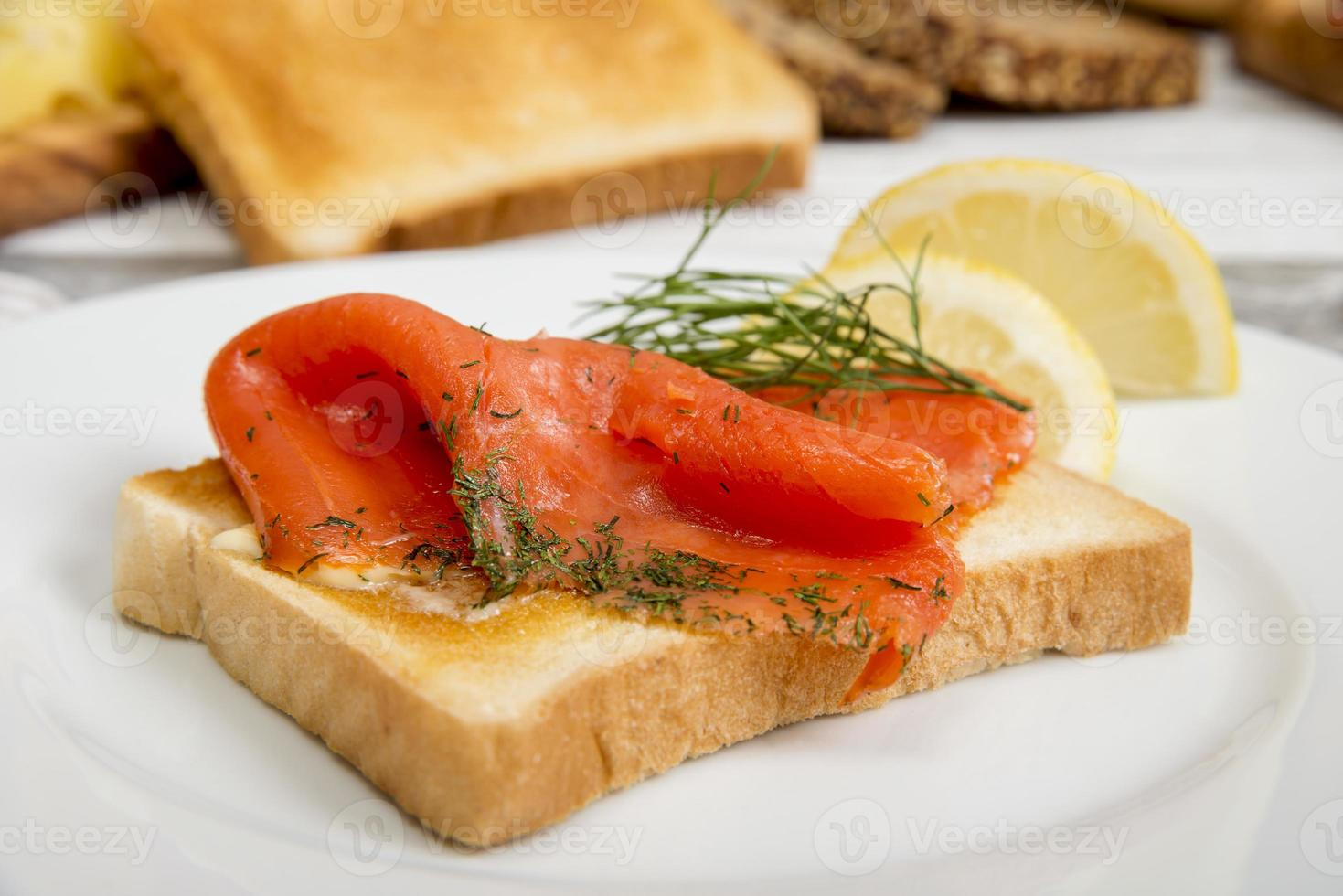 Graved salmon on toast bread with dill and lemon photo
