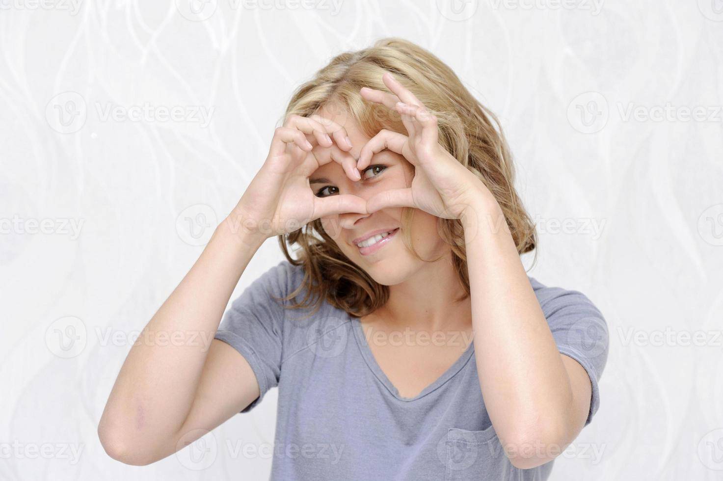 Smiling young woman making heart with fingers photo