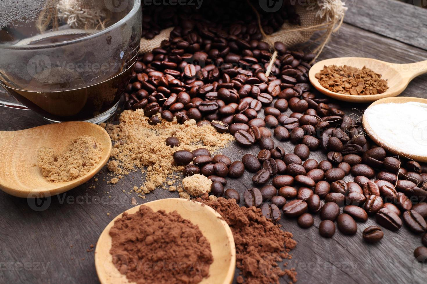 grated coffee in spoon on roasted coffee beans background photo