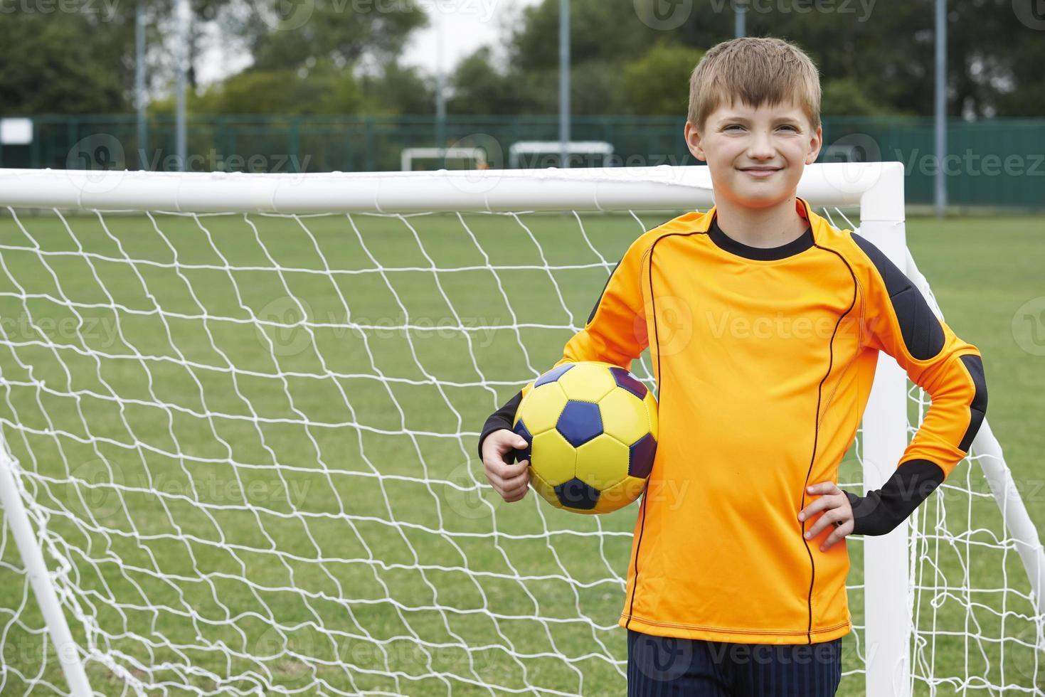 Retrato de portero sosteniendo la pelota en el campo de fútbol de la escuela foto