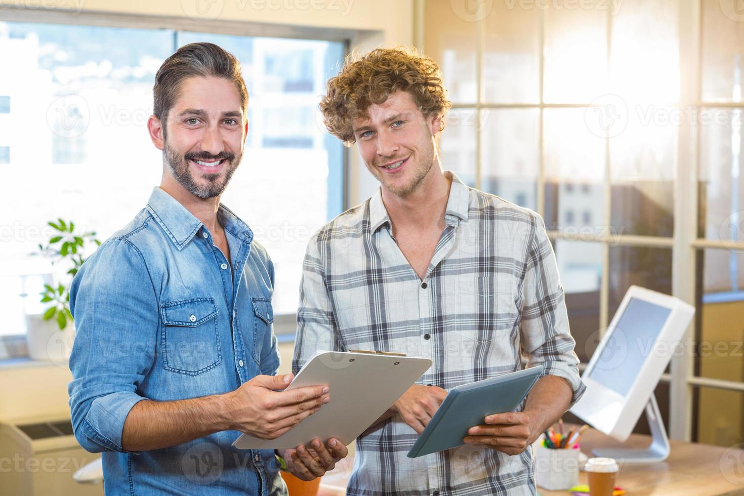 Smiling business team holding clipboard and tablet photo