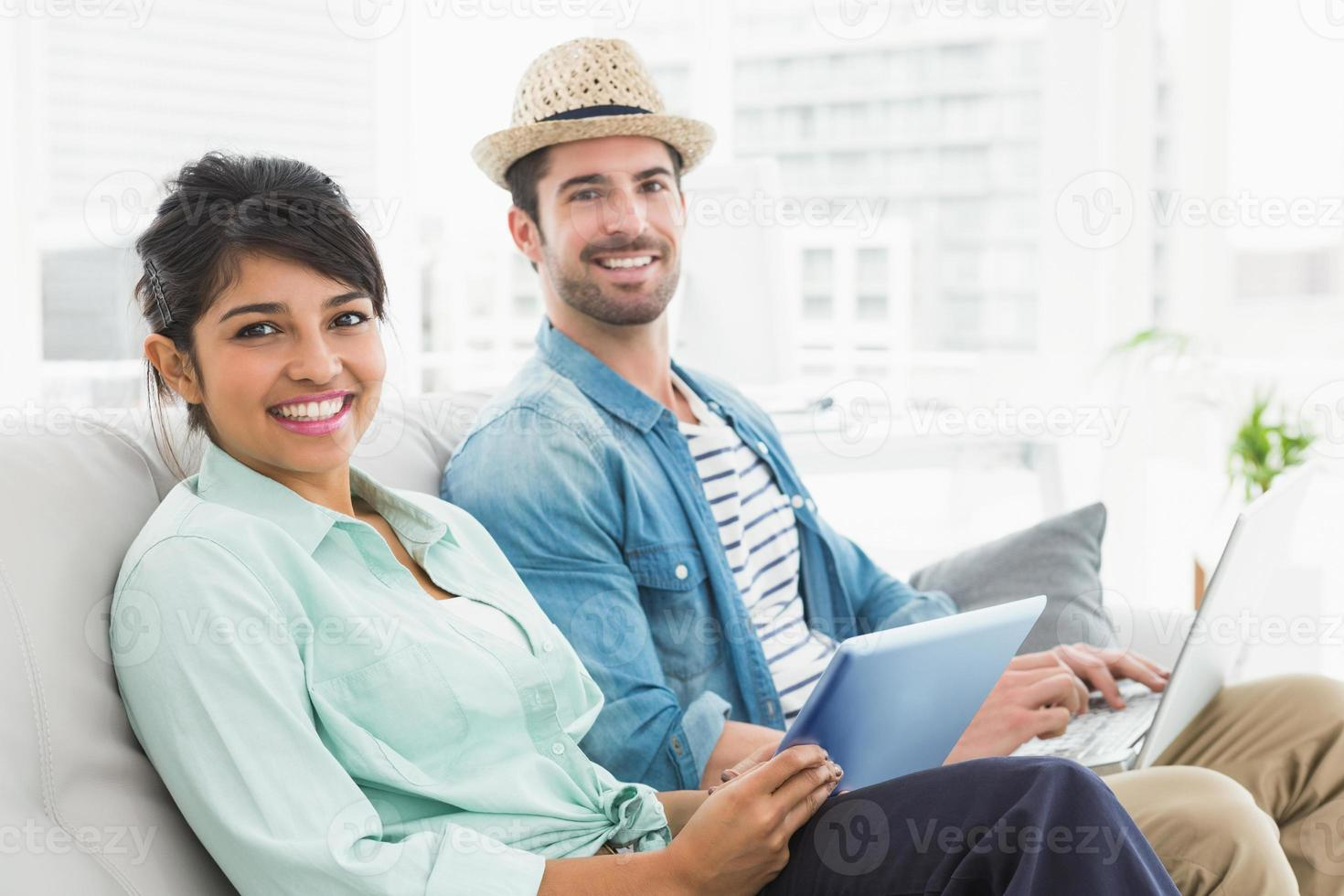 Smiling coworkers using tablet and laptop on couch photo