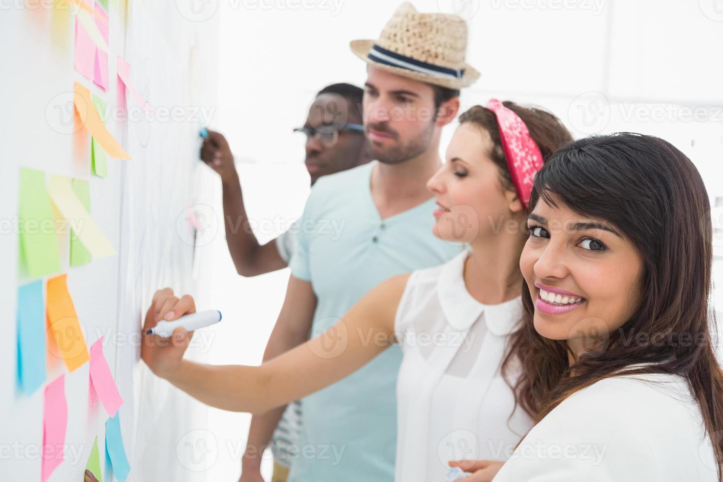 Retrato de mujer sonriente con sus colegas detrás de ella foto