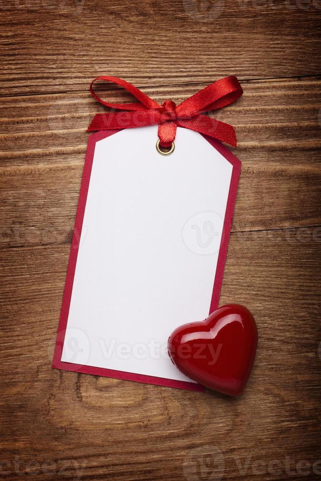 Tarjeta de dirección con arco y corazón sobre fondo de madera vieja. foto