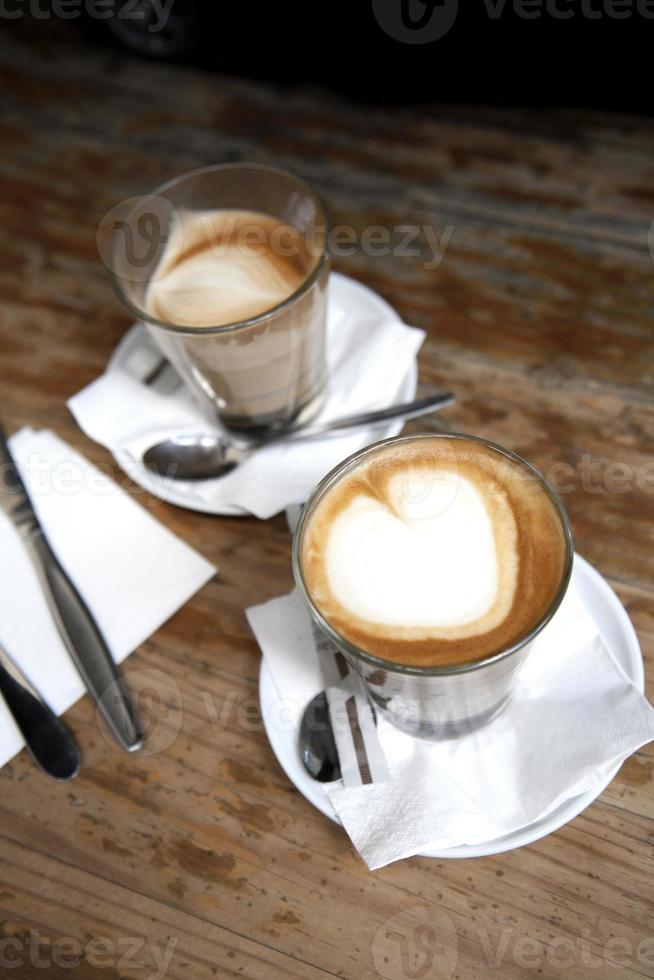 Coffee and cutlery with heart shaped froth photo