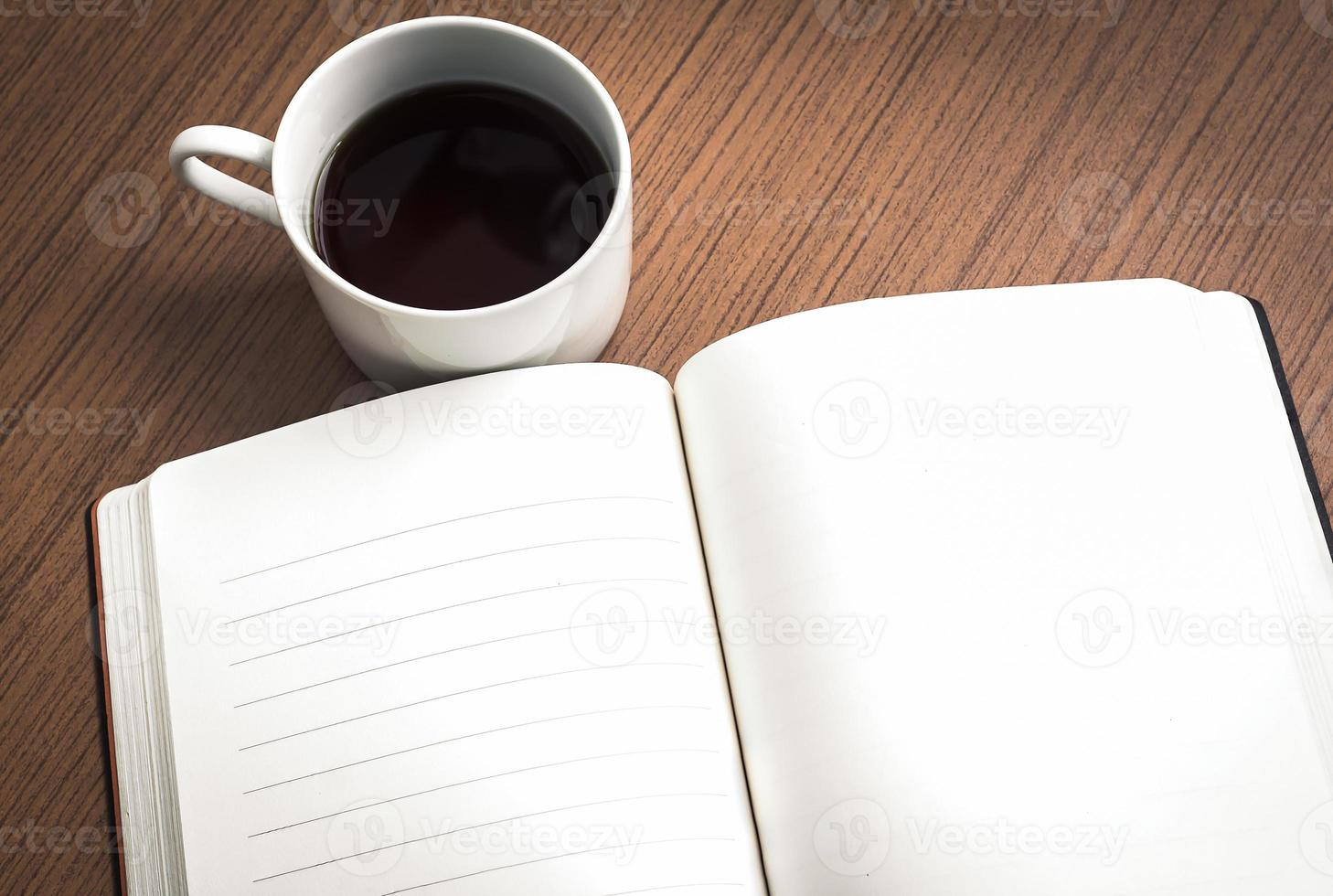 Empty notebook and coffee on wood table photo