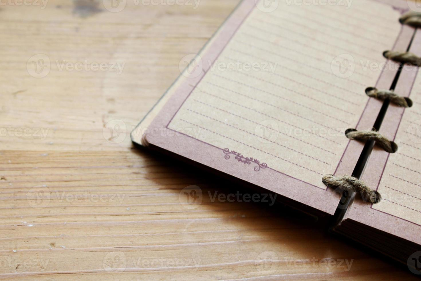 Opened notebook on wooden table photo