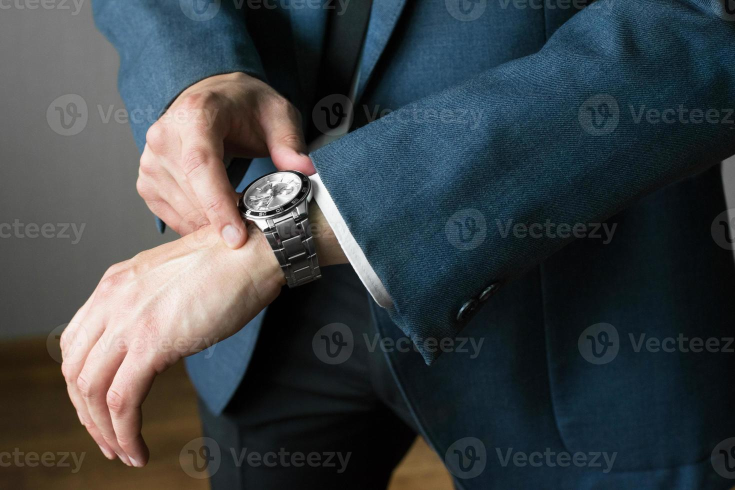 The businessman's photo in a suit. A hand with hours