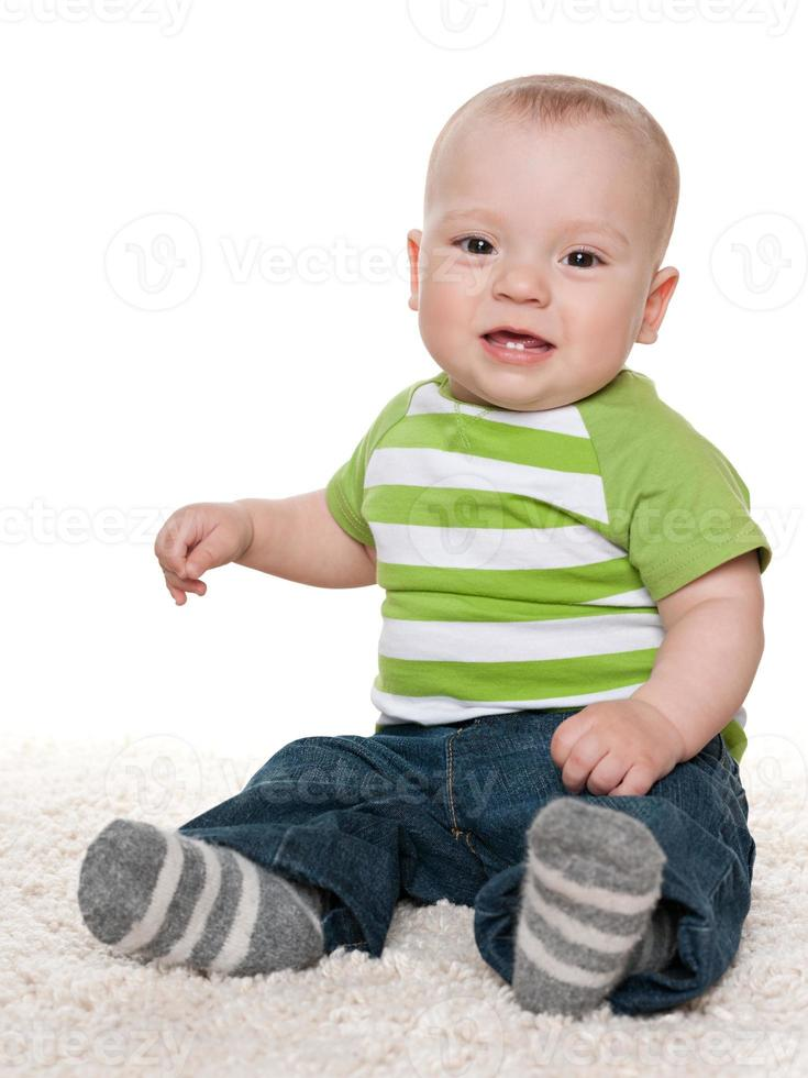 Smiling baby boy sits on the white carpet photo