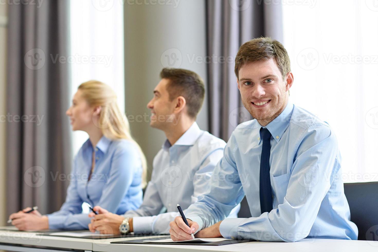 Grupo de empresarios sonrientes reunidos en la oficina foto