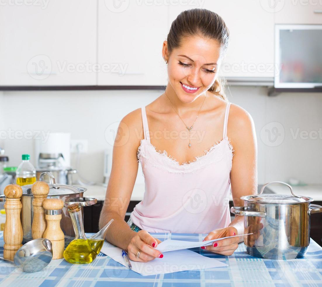 Happy young woman filling papers photo