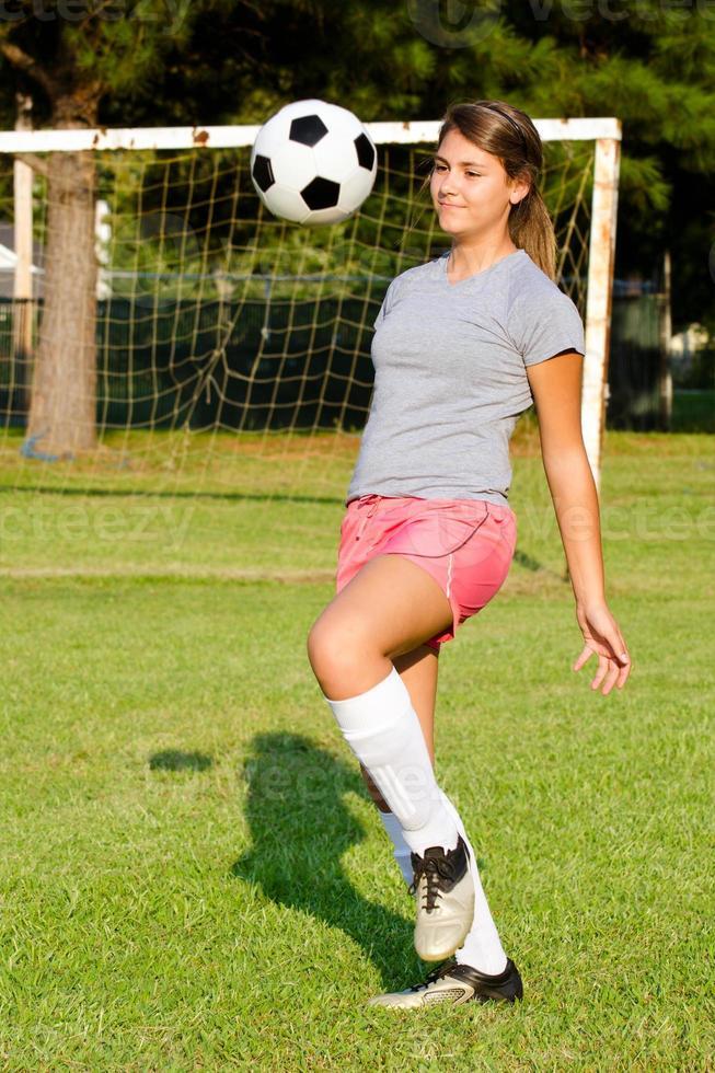 Jovencita haciendo malabares con el balón de fútbol foto