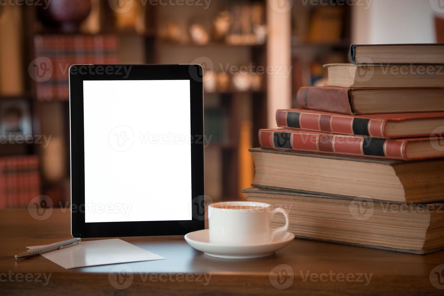 pila de libros antiguos y tableta sobre mesa de madera, foto