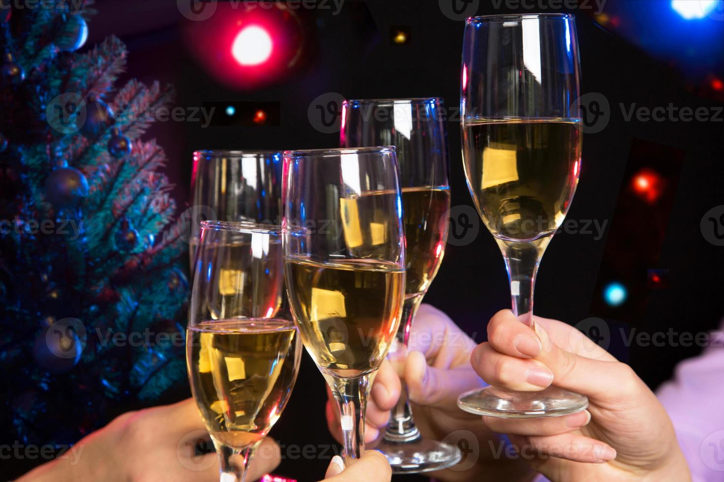 manos de personas con copas de cristal llenas de champán foto