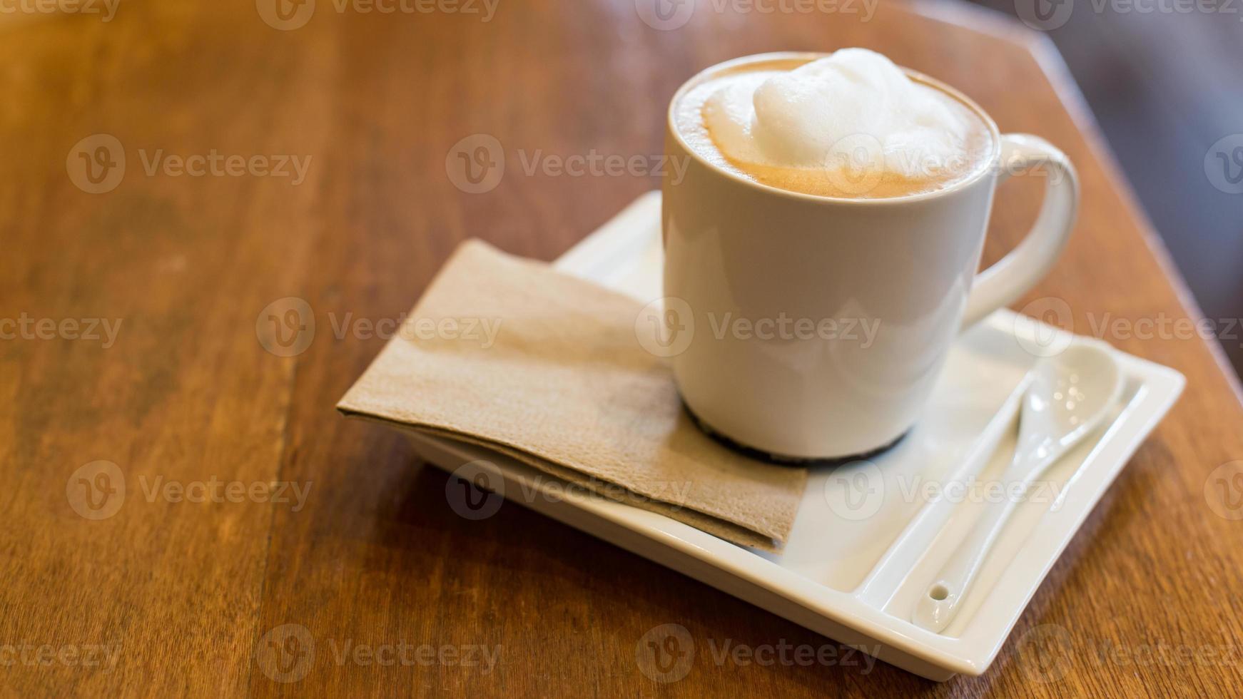 Café con leche en una taza en la mesa de madera. foto