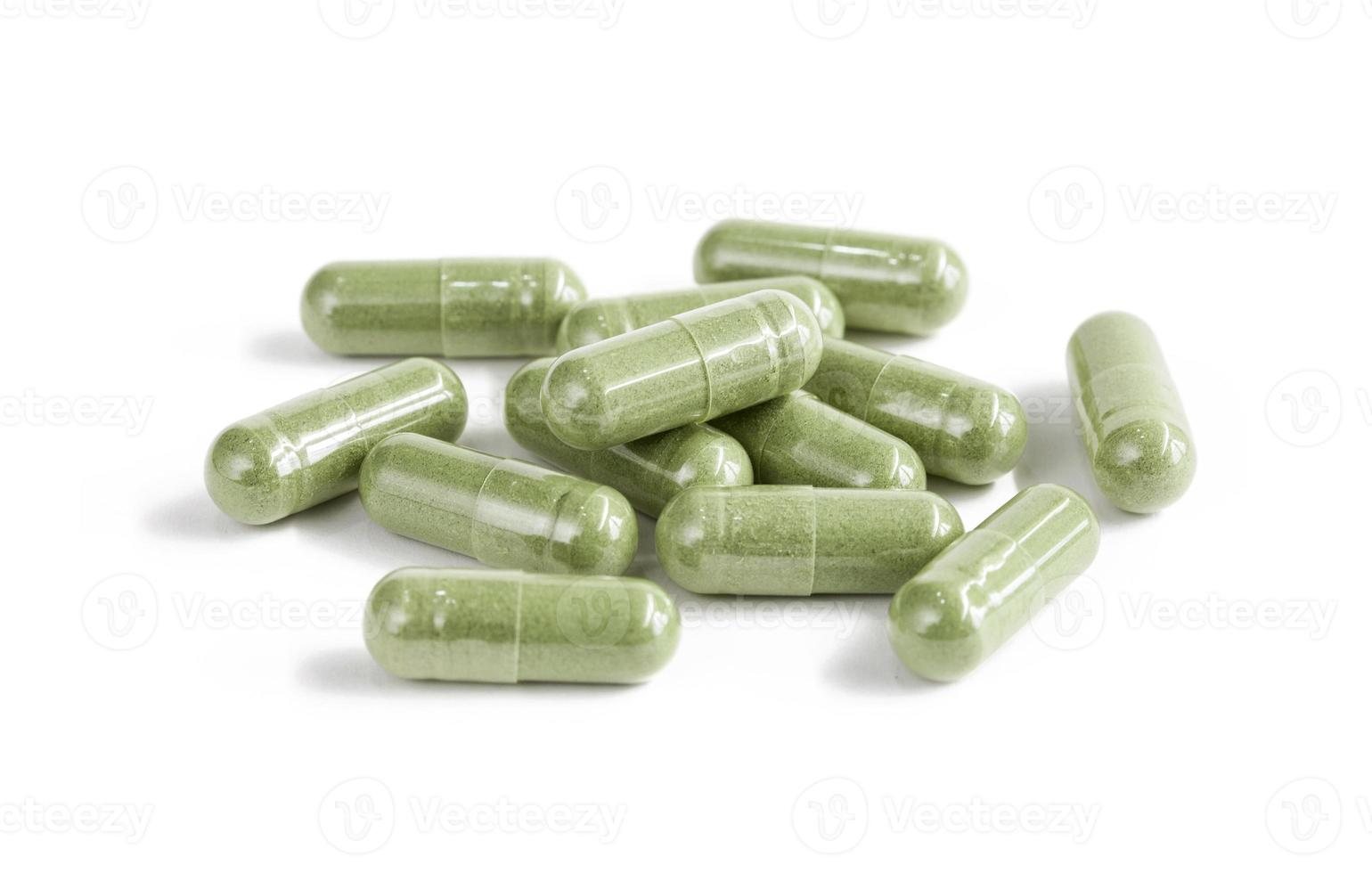 Capsules of green herbal supplement product isolated on white photo