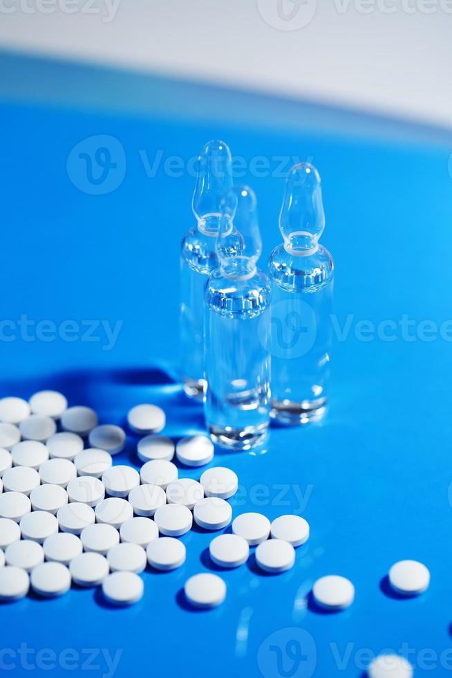 pills. White medical pills on blue background photo