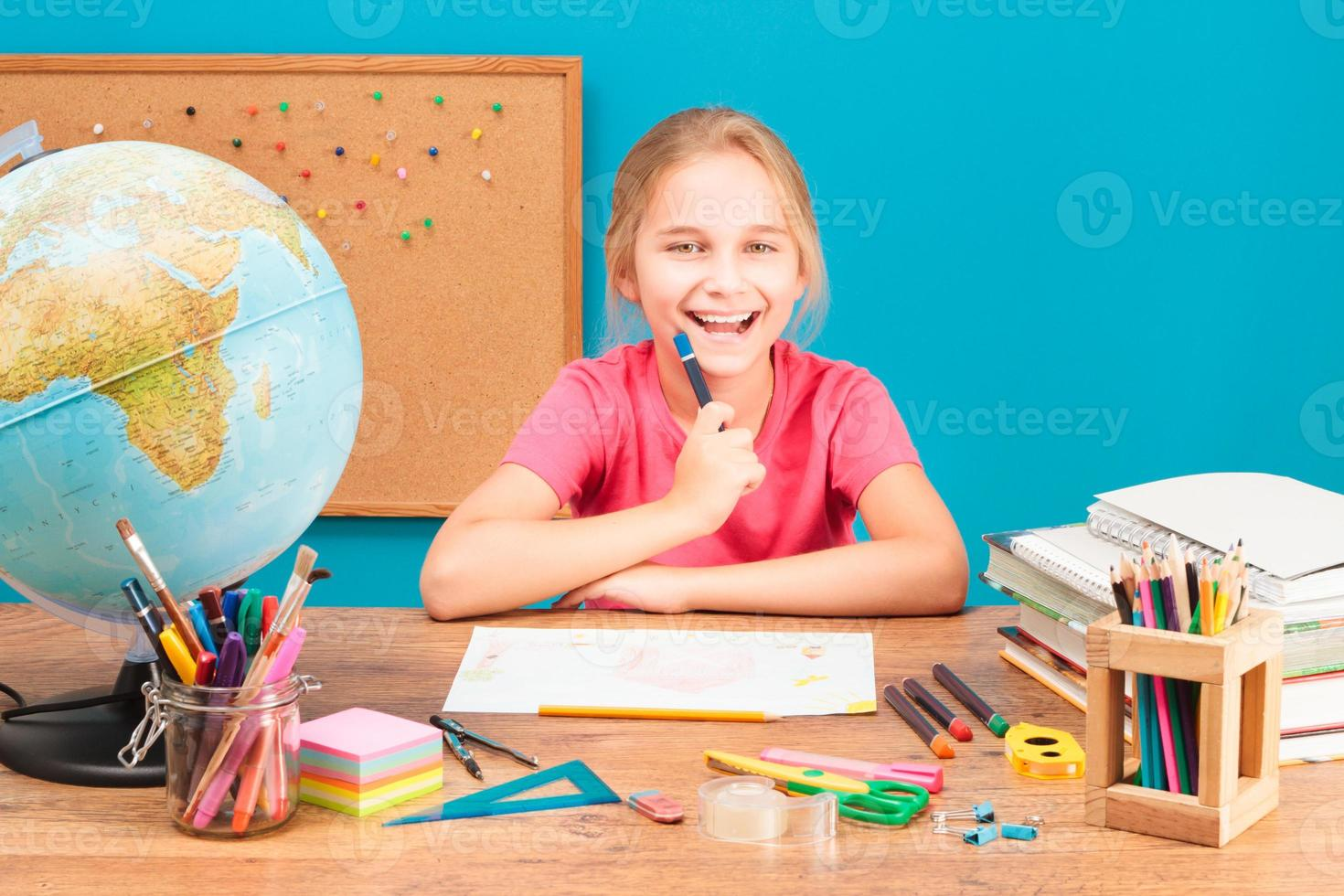 Young smiling girl doing her homework photo