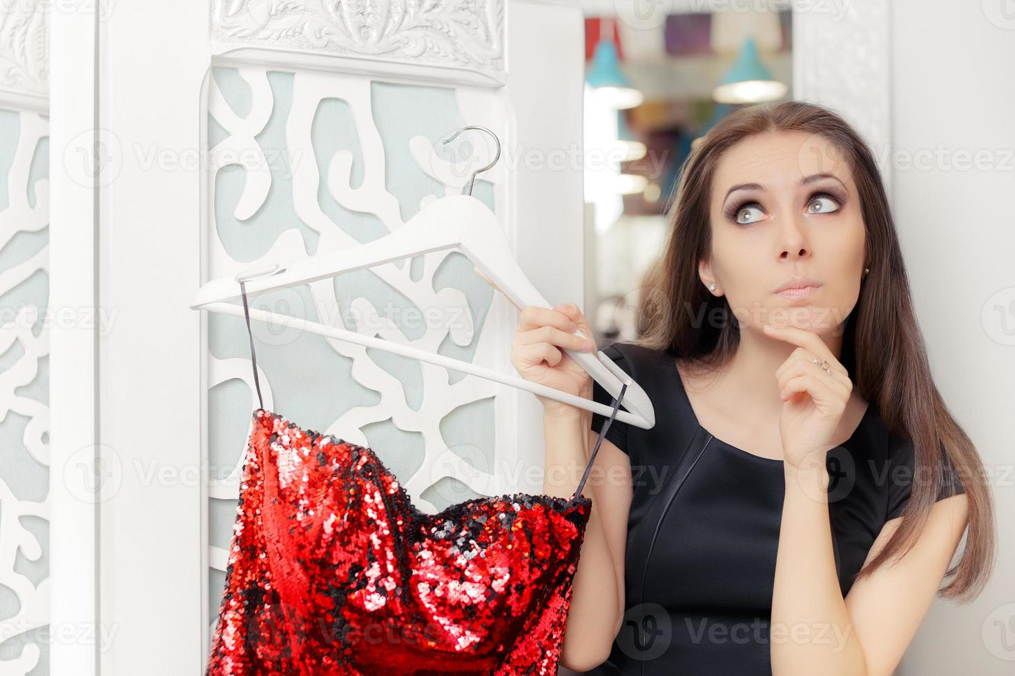 Surprised Girl Trying on Red Party Dress in Dressing Room photo
