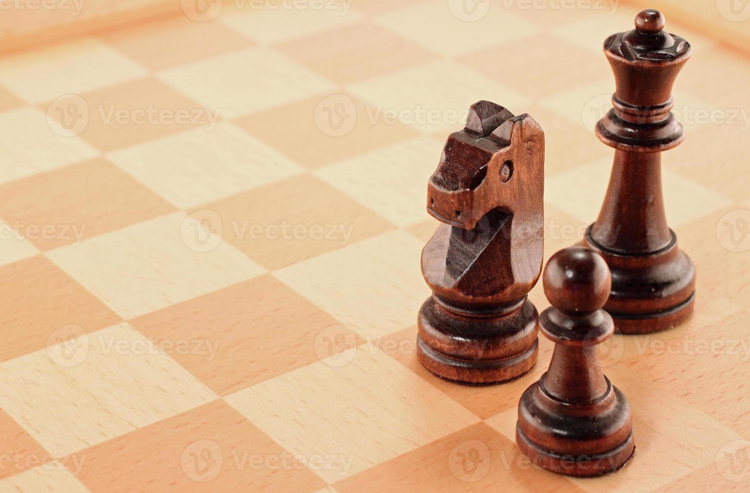 tres piezas de ajedrez de madera en un tablero de ajedrez foto