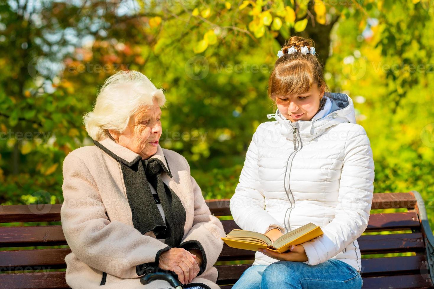 joven nieta lee su libro de abuela anciana foto