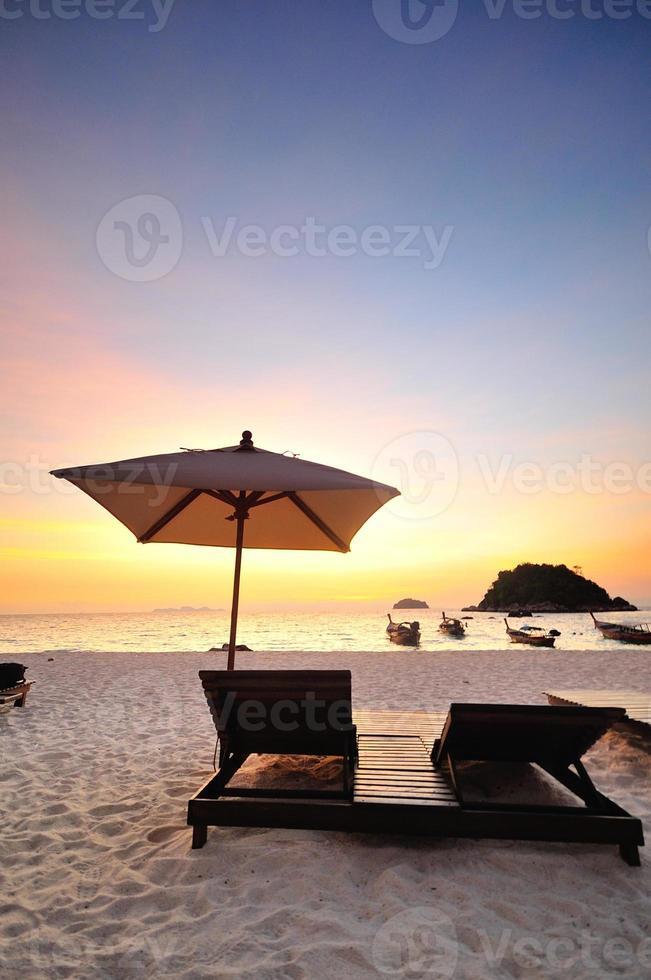 silla de playa y sombrilla en la playa de arena foto