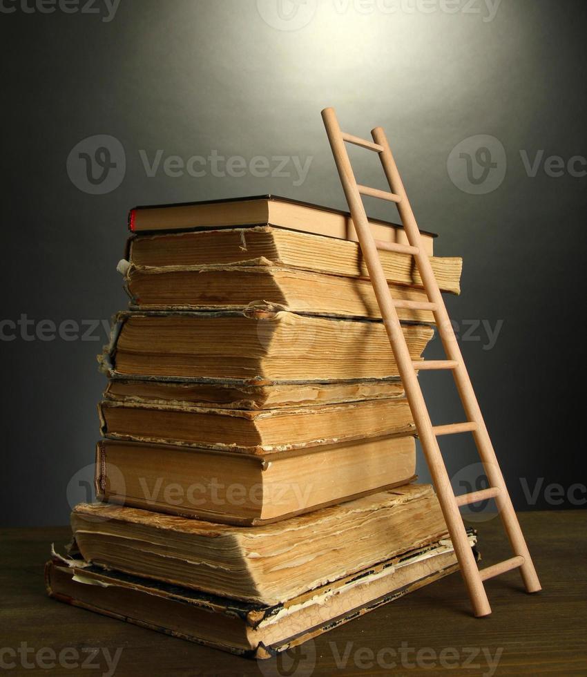 Libros antiguos y escalera de madera, sobre fondo gris foto