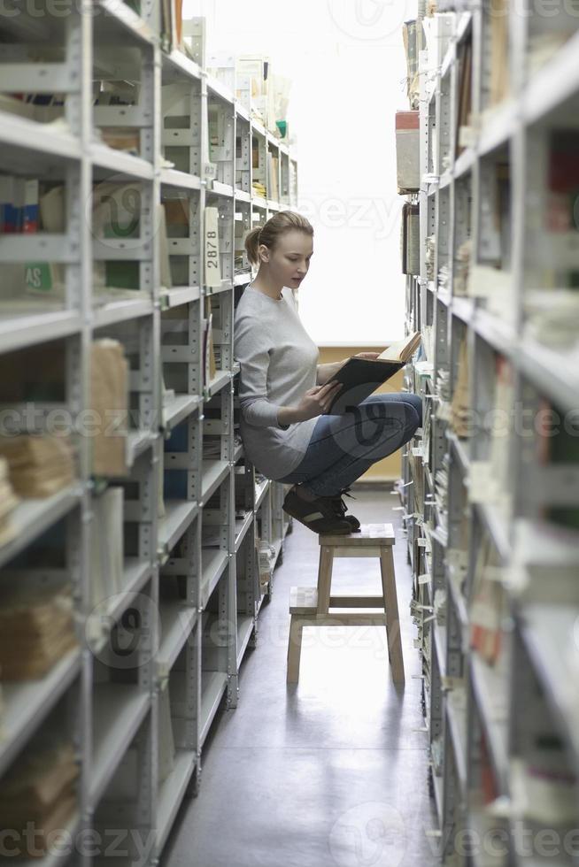 mujer leyendo el libro en el pasillo de la biblioteca foto
