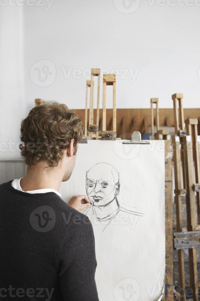 Artist Drawing Charcoal Portrait In Studio photo