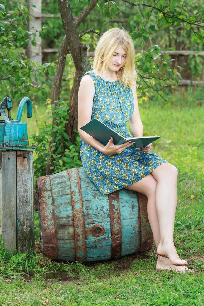 Barefoot student girl in garden reading book with blue cover photo