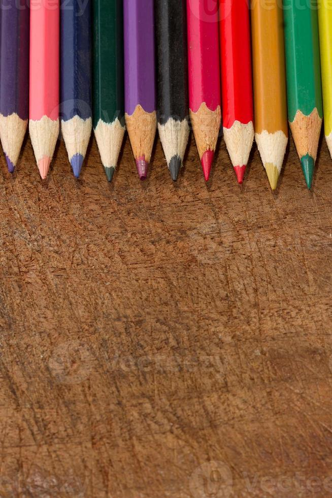 Lápices de colores aislados sobre fondo de madera de cerca foto