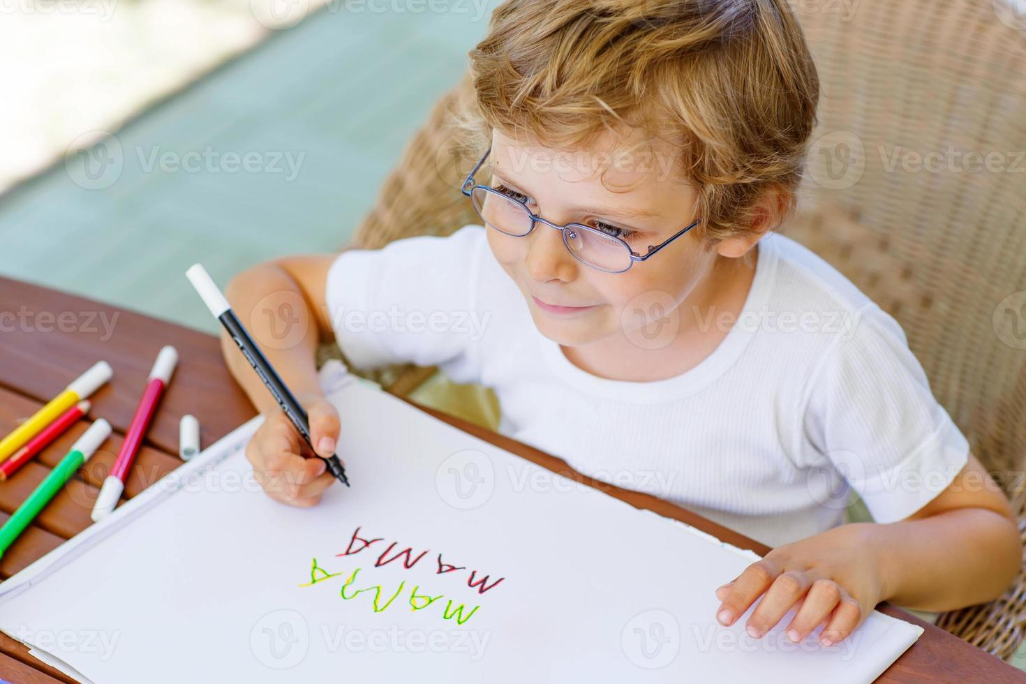 Little boy with glasses making homework at home photo