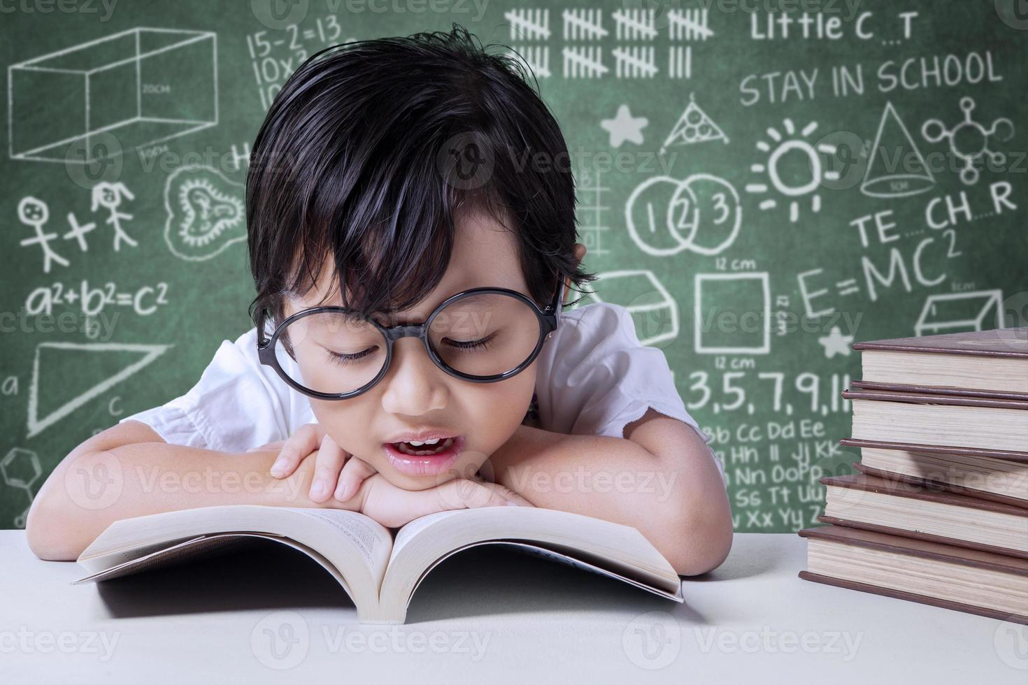 Elementary school student reads textbooks in class photo