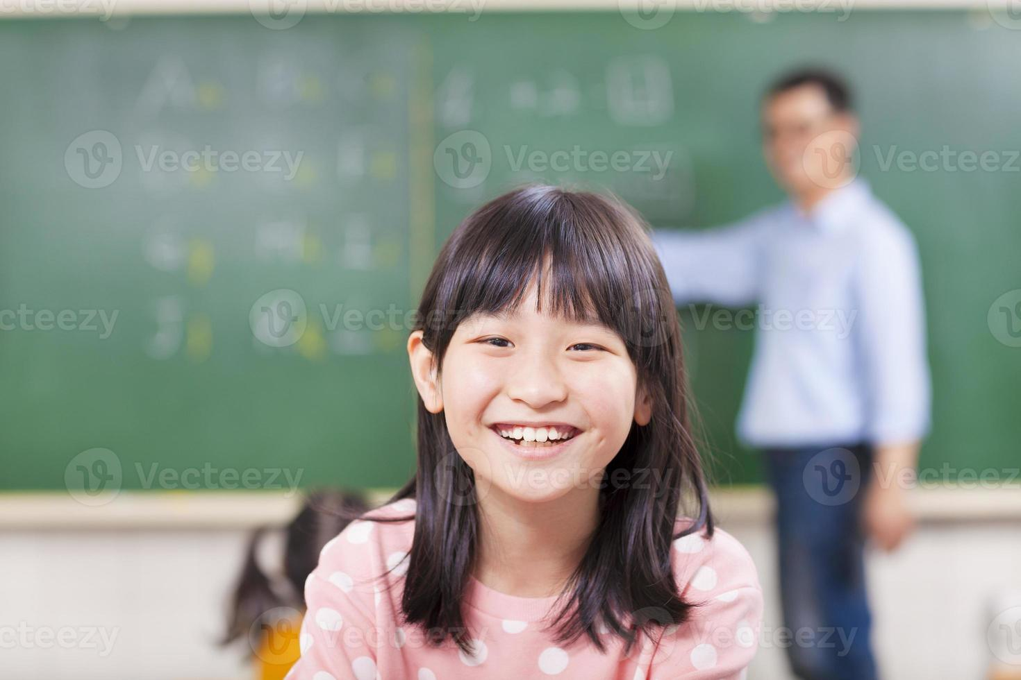 close-up pupils smiling in class with teacher photo