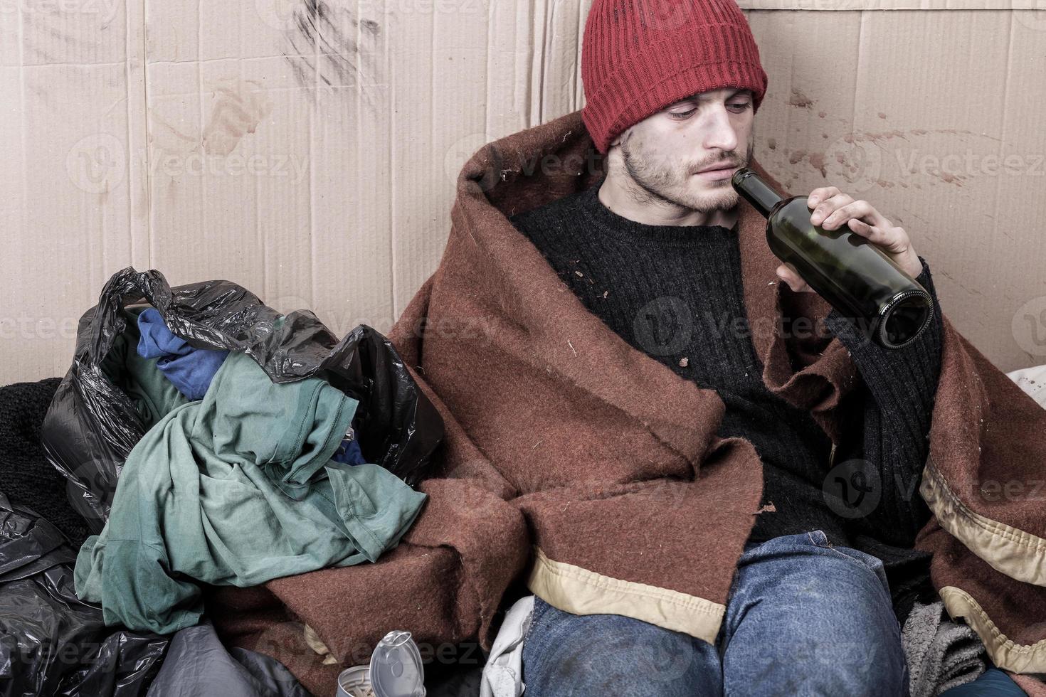 personas sin hogar bebiendo vino barato foto