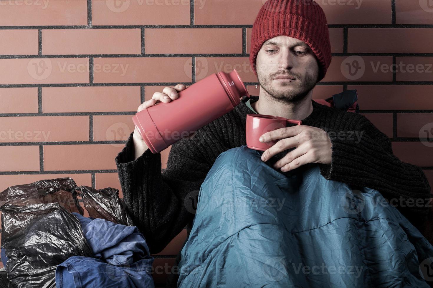 personas sin hogar bebiendo té caliente foto