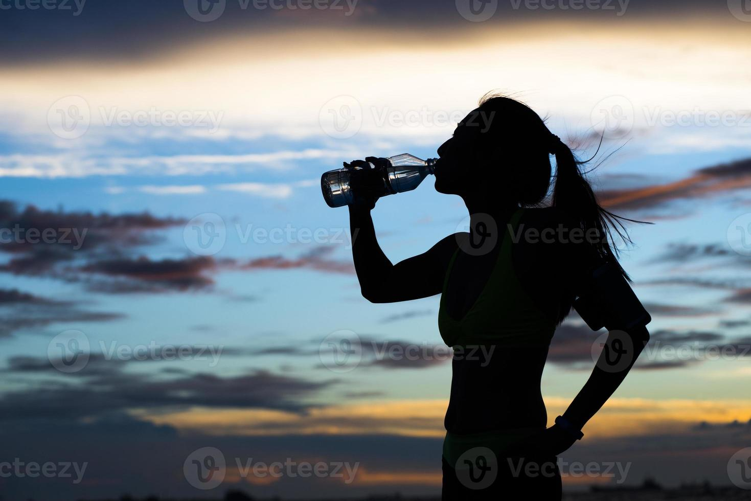 Runner drinks water after training photo